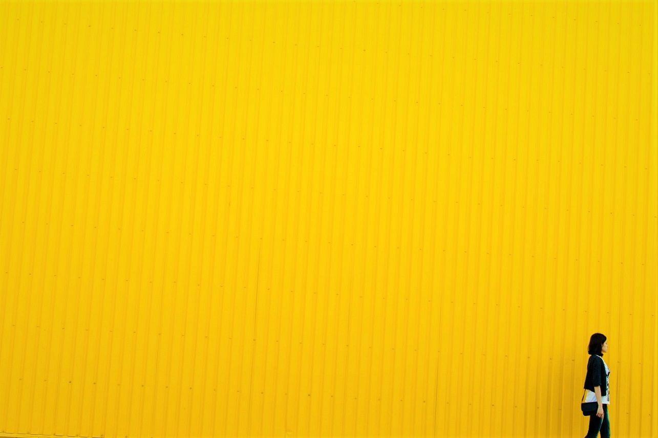 Xantofobia Chica paseando delante de Pared de Color Amarillo